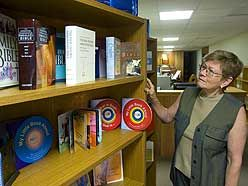 Librarian Rita Eman examines some of the books available at the Christian Science Reading Room. (MIKE HENSEN, The London Free Press)